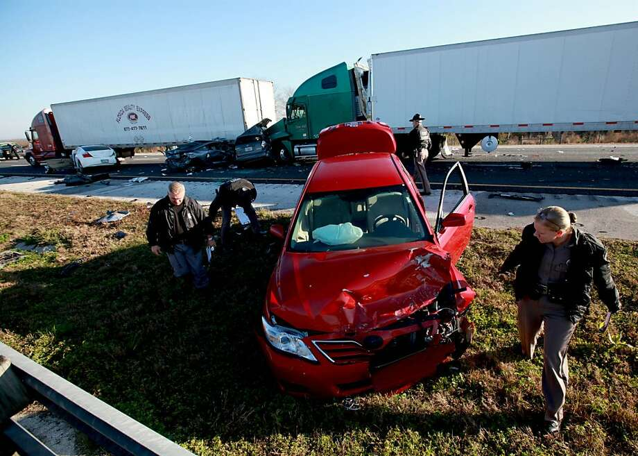 Officials work at the scene of a multi-vehicle wreck on Interstate 75 at Paynes Prairie on Sunday, Jan. 29, 2012, south of Gainesville, Fla.  (AP Photo/Matt Stamey, The Gainesville Sun) Photo: Matt Stamey, Associated Press