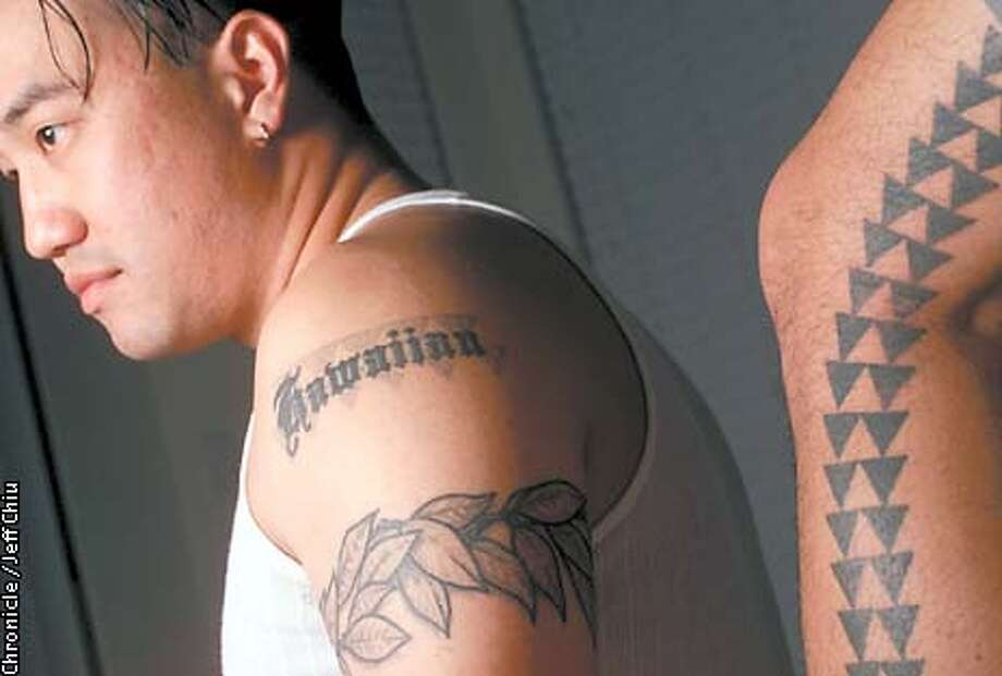 Kris Kahono, 28, (left) and his brother Kapono Kahono, 23, show their tattoos on on Thursday afternoon at Kris' house in Redwood Shores. Kris has the same tattoo on his left leg as Kapono. The Kahono brothers are some of the growing number of young Polynesian men and women to get tattoos as a rite of passage. Photo by Jeff Chiu / The Chronicle. Photo: Jeff Chiu