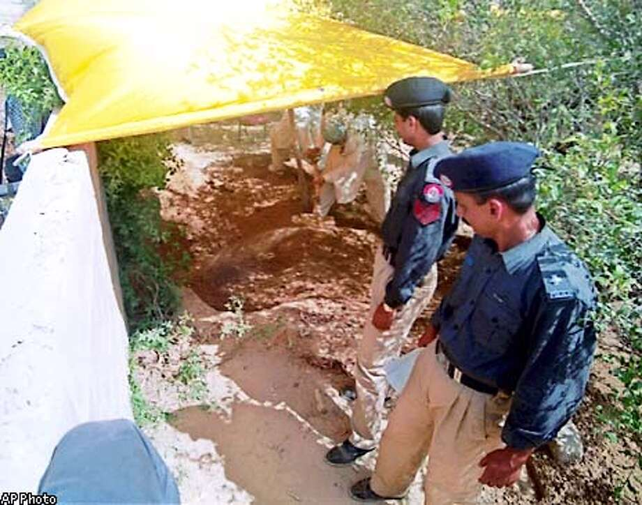 Police officers look as workers pour dirt in a burial place Friday, May 17, 2002 near Karachi, Pakistan. A dismembered body authorities believe to be that of Wall Street Journal reporter Daniel Pearl was removed Friday from the shallow grave on property owned by a group identified as a terrorist organization by the United States. Blood and hair samples were sent for DNA testing to confirm whether it was Pearl's body.(AP Photo)