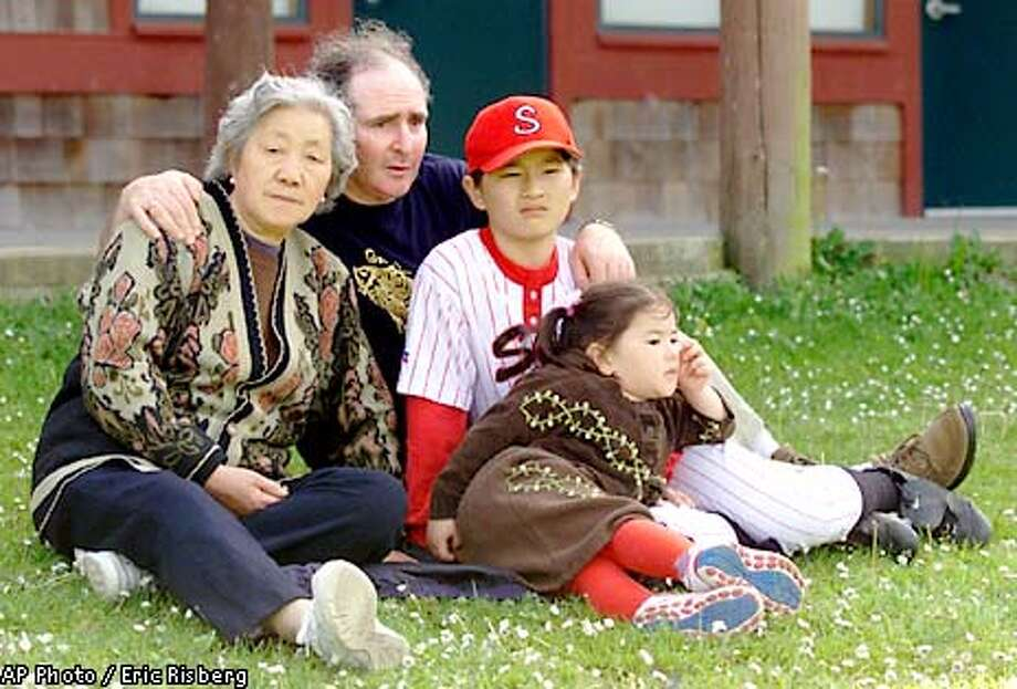 John Mark, second from left, sits with his mother-in-law, 73-year-old Zhenfu Ge, along with his son, Yichao Wang, and daughter Lily Wang Mark, while waiting for a Little League game to begin in Sausalito, Calif., Wednesday, April 25, 2001. Because Mark's wife, Yanyu Wang, died earlier this month, Zhenfu Ge has lost her legal right to stay in America and faces deportation to China.(AP Photo/Eric Risberg) Photo: ERIC RISBERG