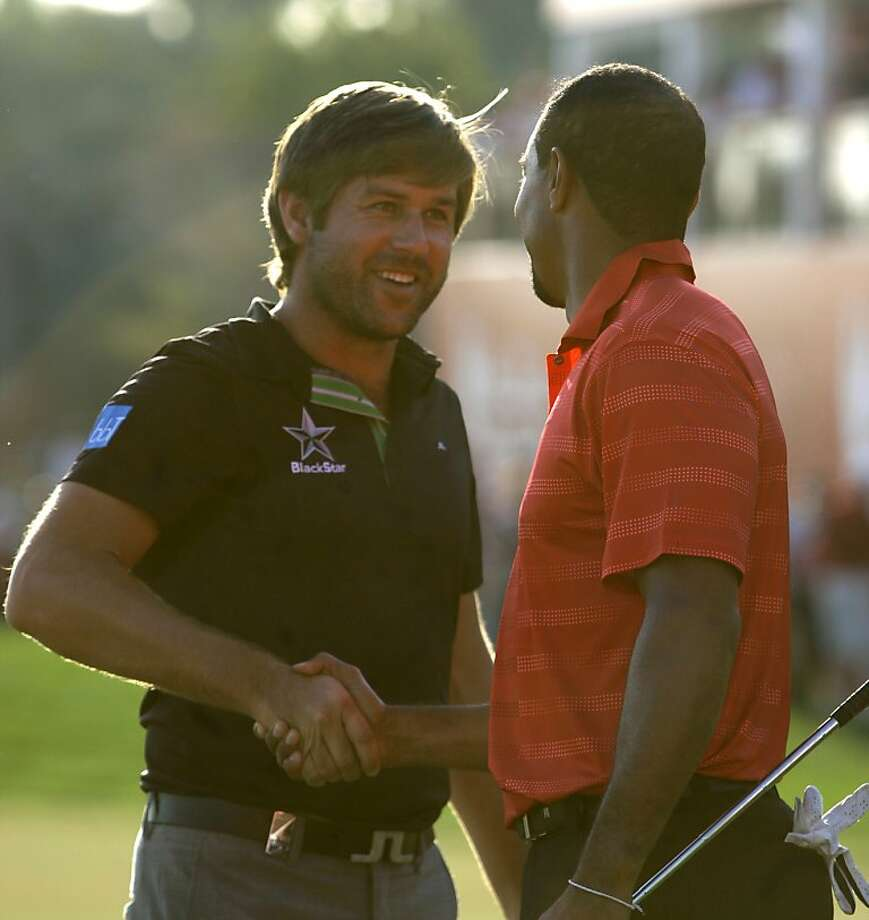 Robert Rock from England, left,  shakes hands with Tiger Woods after he won the Abu Dhabi HSBC Championship, Sunday, Jan. 29, 2012 in Abu Dhabi, United Arab Emirates.  Rock won the trophy, Woods taking a shared third place. (AP Photo/Kamran Jebreili) Photo: Kamran Jebreili, Associated Press