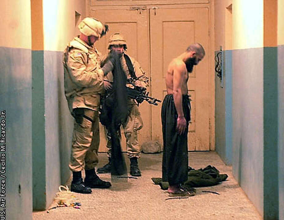 (NYT17) MAZAR-E-SHARIF, Afghanistan -- Dec. 27, 2001 -- ATTACK-AFGHAN -- Members of the U.S. Air Force search through the clothes of a Taliban detainee in Mazar-e-Sharif, Afghanistan, in a recent but undated photo provided by the Air Force. Detainees were being prepared for transportation to Camp Rhino, near Kandahar. Defense Secretary Donald H. Rumsfeld said Thursday that the U.S. military will hold Taliban and al-Qaida detainees at the Navy base in Guantanamo, Cuba, but has no plans to use it as a site for military tribunals. (Cecilio M. Ricardo Jr./U.S. Air Force/The New York Times) Photo: CECILIO M. RICARDO JR.