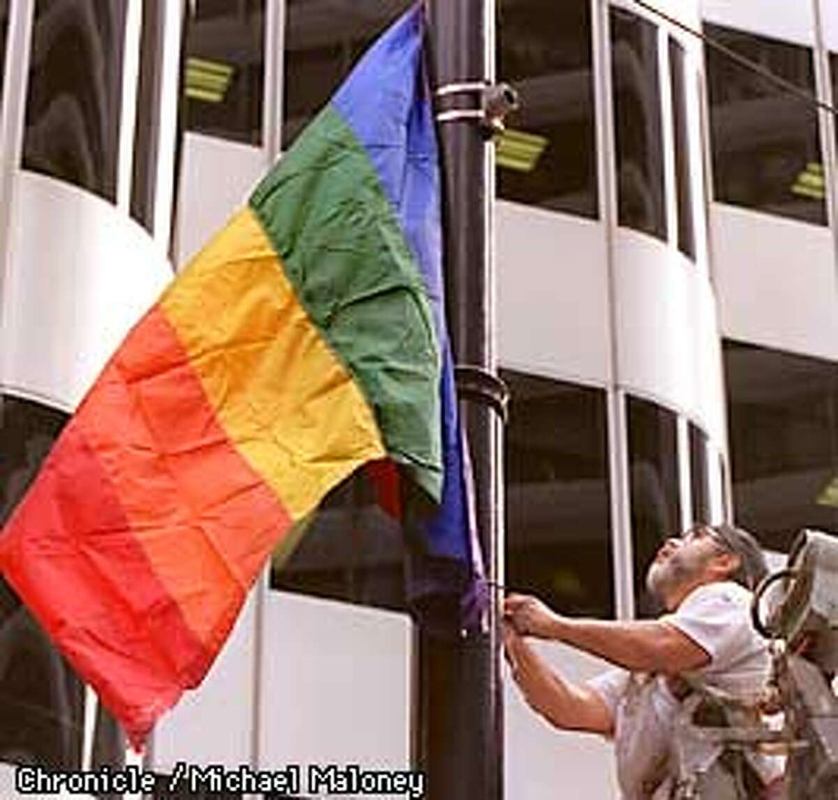 Feliciano Berny of Giampolini and Company (painting contractor) attaches 150 rainbow flags to lightpoles along Market Street. The flags will line the Gay Freedom Day parade route. Photo by Michael Maloney