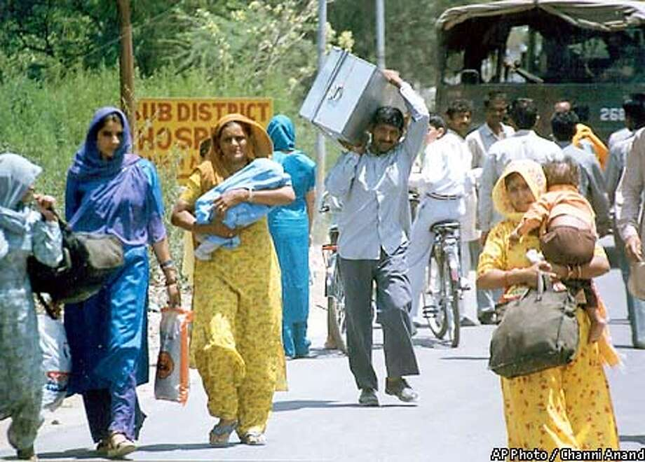 Indian border villagers carry their belongings as they migrate to safer areas in Hiranagar, near the Indian border city of Jammu, India, Saturday, May 18, 2002. Firing between the two nuclear-armed neighbors India and Pankistan escalated in the disputed Kashmir region, forcing thousands of villagers to flee. Two people were killed as both sides fired at each other across the frontier. (AP Photo/Channi Anand) Photo: CHANNI ANAND