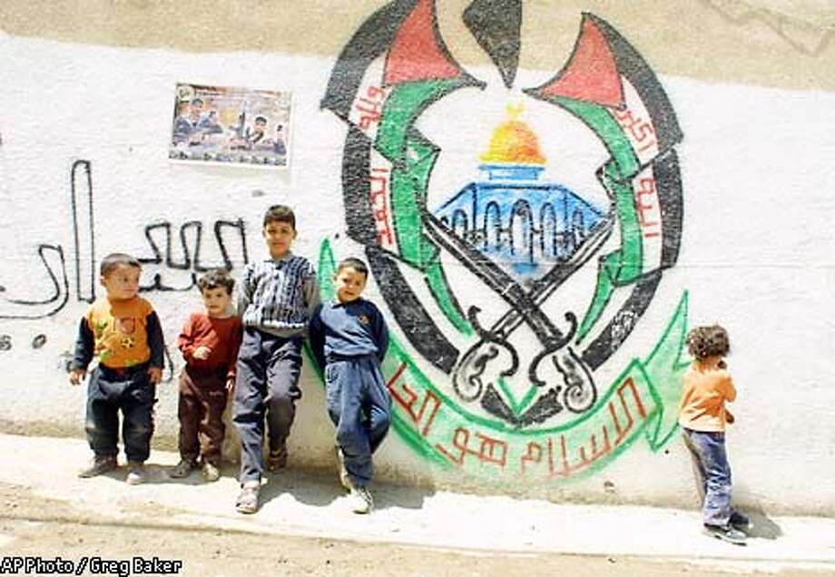 Palestinian children stand in front of the painted logo of Hamas on a wall at the Jenin refugee camp in the West Bank Sunday, April 28, 2002. Israel approved a U.S. proposal aimed at ending the month-old siege of Palestinian leader Yasser Arafat's compound, but said it would bar a U.N. fact-finding mission from examining what happened in the battle at the Jenin refugee camp. (AP Photo/Greg Baker) Photo: GREG BAKER