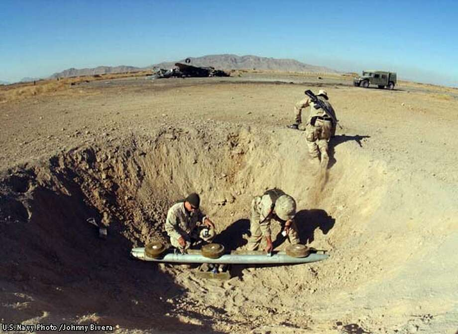 At a forward operating base in Kandahar, Afghanistan, Explosive Ordnance Disposal personnel prepare charges to blow up stockpiled bombs left behind by fleeing Al Qaida troops, December 23, 2001. U.S. Navy EOD personnel are conducting missions in support of Operation Enduring Freedom. Picture released December 26. U.S. Navy Photo /Johnny Bivera Photo: POOL