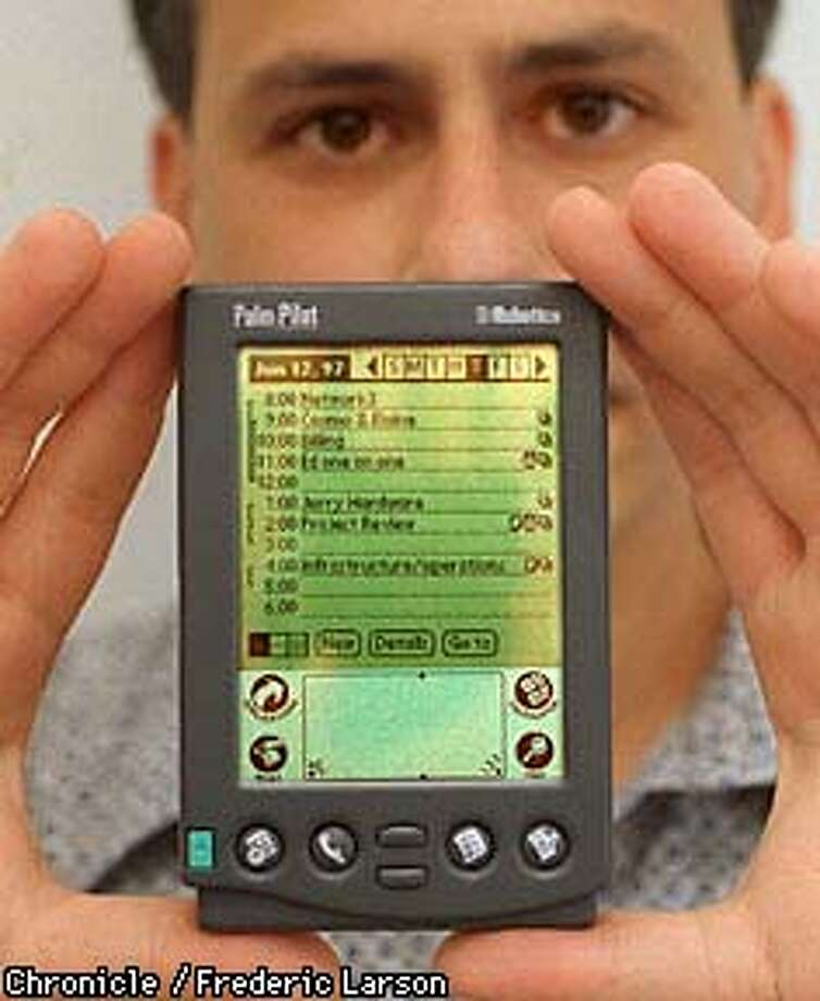 PILOT/12JUN97/MN/FRL: Product manager Joe Sipher of U.S Robotics holds up their PalmPilot handheld computer. Chronicle photo by Frederic Larson.
