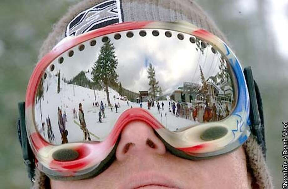 The terrain around Squaw Valley is reflected in the goggles of Mark Broderick as he waits for his brother Sunday. Great skiing and a break in the weather attracted thousands to the slopes. By Brant Ward/Chronicle Photo: BRANT WARD