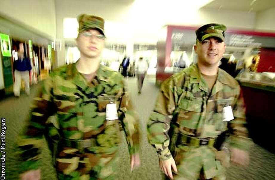 Jacquelyn Ambrogio and Robert Paolitti walk through the airport in San Francisco. It's been more than 3 months since sept 11 and the national guard is still out at sfo and 27 other airports in california. We want to talk to some of these guardsmen & women, who signed up to be weekend warriors. Now they have an open ended assignment they never anticipated. the rest of us will be home for christmas; they'll be on guard.Photo By Kurt Rogers Photo: Kurt Rogers