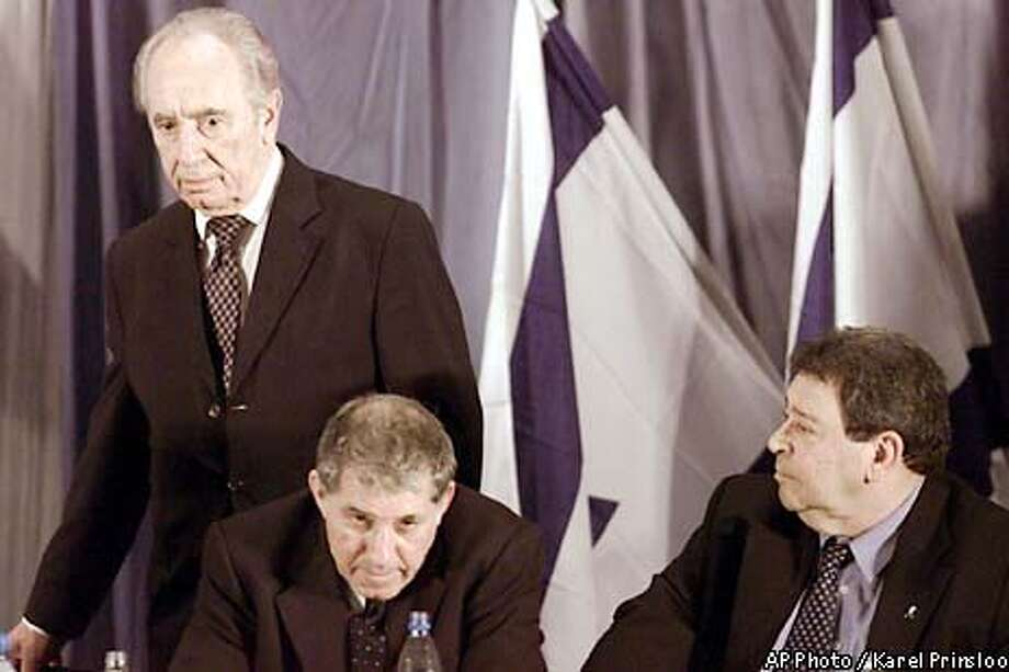 Israeli Foreign Minister, Shimon Peres stands to address a Labor Party convention, Wednesday, May 15, 2002 in a suburb of Tel Aviv where party chairman and defense minister Binyamin Ben-Eliezer, right, presented his ideas for a peace agreement between Israel and the Palestinians. At center is Ranaan Cohen, a Labor party member. (AP Photo/Karel Prinsloo) Photo: KAREL PRINSLOO