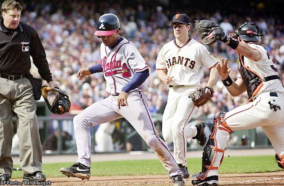 Atlanta Braves' Rafael Furcal, second from left, is tagged out at the plate by San Francisco Giants catcher Benito Santiago, right, in the third inning Wednesday May 15, 2002, at Pacific Bell Park in San Francisco. Watching are home plate umpire Gary Cederstrom, left, and Giants third baseman David Bell, who assisted the play. Furcal was trying to score from third base on a grounder by Gary Sheffield. (AP Photo/Ben Margot) Photo: BEN MARGOT
