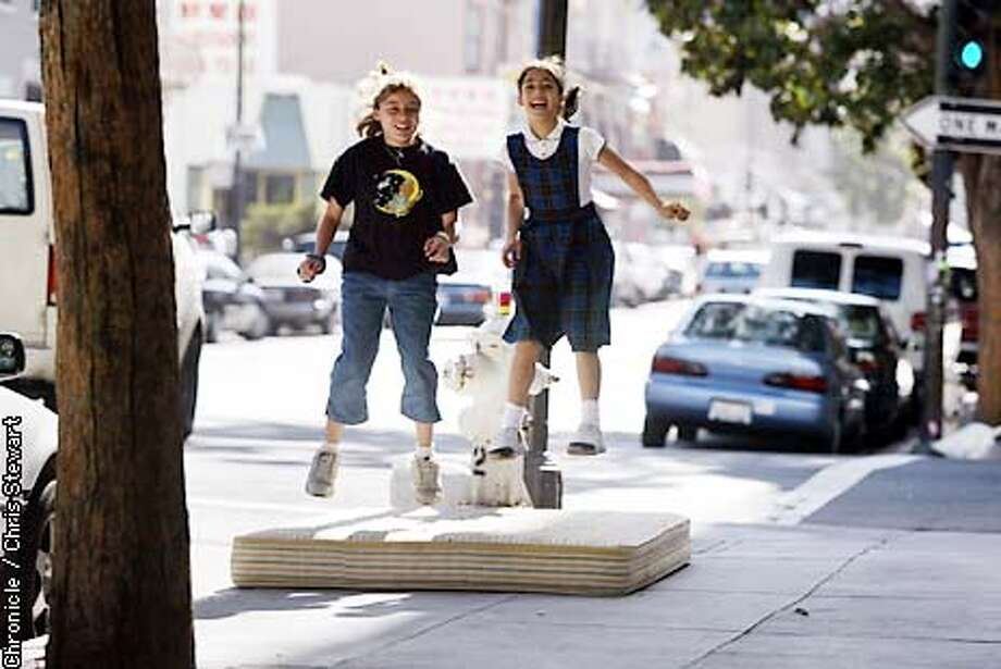 A discarded mattress becomes an impromptu trampoline on a warm Tenderloin afternoon for Arianna Valle, 12 (L), and Rosie Fernandez, 9. The youngsters found the mattress on the sidewalk at Ellis and Hyde Streets. BY CHRIS STEWART/THE CHRONICLE Photo: CHRIS STEWART