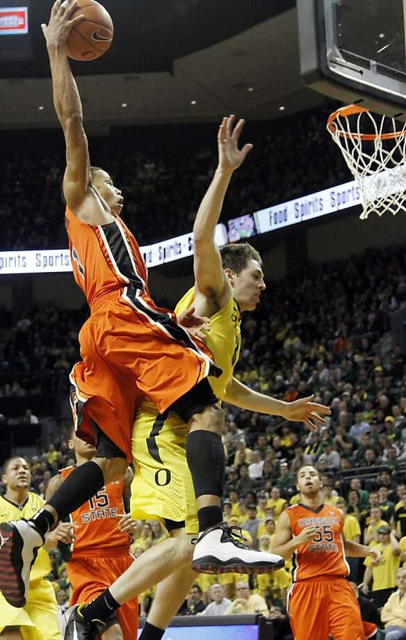 Oregon State guard Jared Cunningham, left, goes to the basket over Oregon guard Garrett Sim during the second half of an NCAA college basketball game in Eugene, Ore., Sunday, Jan. 29, 2012. Cunningham led Oregon State in scoring with 27 points in the team's 76-71 win. (AP Photo/Don Ryan) Photo: Don Ryan, Associated Press