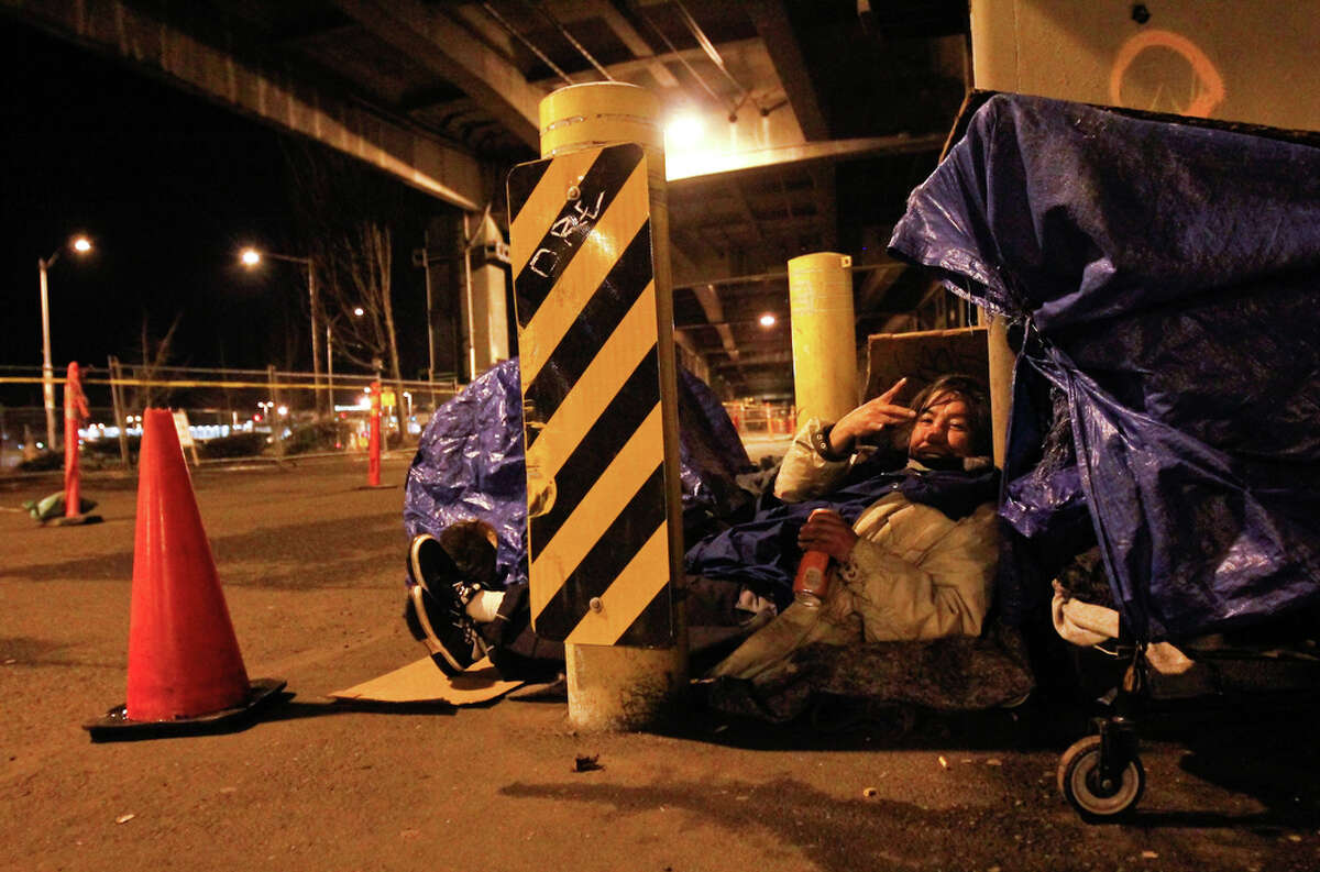 Stephan reclines near the Alaskan Way Viaduct in Seattle on Friday, Jan. 27, 2012. Local volunteers and organizations along with the Seattle/King County Coalition on Homelessness attempted to count all unsheltered homeless people throughout King County as part of the 32nd annual One Night Count on Friday Jan. 27, 2012. An estimated 800 volunteers thoroughly combed the streets of King County, finding that 2,594 men, women and children had no shelter.