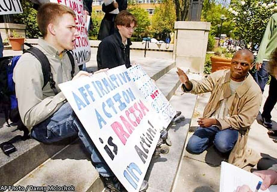 "Affirmative action proponent Rev. Valdiveso Matthews, right, from the Eqlise Gnostique church, argues with University of Michigan student James Justin Wilson, left, holding a sign stating ""Affirmative Action is Racism in Action"" on the steps of the Michigan Union on the University of Michigan Campus Tuesday May 14, 2002 in Ann Arbor, Mich. Jared Suess sits next to Wilson holding a sign stating ""Content of Character not color of skin"" A sharply divided federal appeals court on Tuesday upheld the University of Michigan law school's use ofrace in admissions, a decision one legal observer called a ``stepping stone to a landmark decision'' before the U.S. Supreme Court. (AP Photo/Danny Moloshok) Photo: DANNY MOLOSHOK"