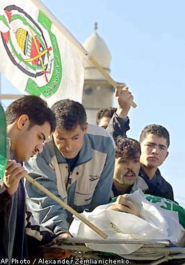 Palestinian Islamic Jihad supporter Zakaria Al Nawaja, 15, shot on Friday during a funeral procession by Palestinian police, is carried away by mourners as a Fatah flag waves over his body outside the Gaza City hospital Saturday, Dec. 22, 2001. Nawaja was one of six Palestinians buried today in six separate funerals that ended peacefully following two days of clashes between Palestinian police _who have been trying to enforce a cease fire_ and supporters of Hamas and Islamic Jihad group. In all seven Palestinians have been shot and 94 hurt in internal confrontations since Thursday. (AP Photo/Alexander Zemlianichenko) Photo: ALEXANDER ZEMLIANICHENKO