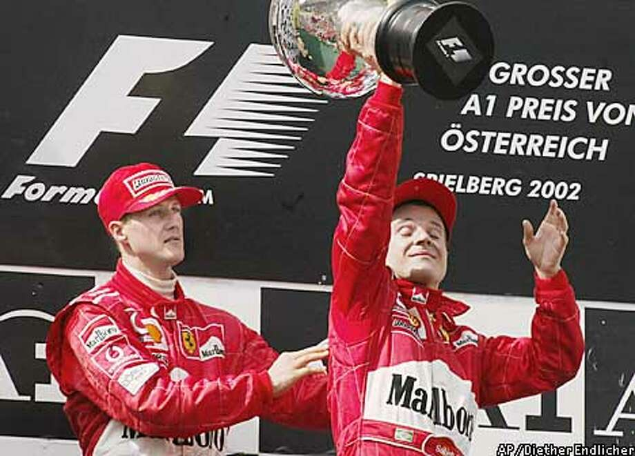 Winner Michael Schumacher of Germany pushes his Ferrari teammate and second place finisher Rubens Barrichello to the winner's position during the victory ceremony for the Austrian Grand Prix Formula One race at the Austria Ring race track in Spielberg, Austria, Sunday, May 12, 2002. Schumacher won the race when Barrichello let him pass just before the checkered flag. Barrichello, who had led from the start, received orders from his team to let Schumacher win.(AP Photo/Diether Endlicher) Photo: DIETHER ENDLICHER