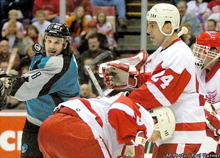 San Jose Sharks center Mike Ricci, left, takes a swing at a airborne puck in front of Detroit Red Wings defenseman Chris Chelios (24) and goalie Dominik Hasek, far right, in the second period on Friday, Dec. 21, 2001 at Joe Louis Arena in Detroit. (AP Photo/Paul Warner) Photo: PAUL WARNER