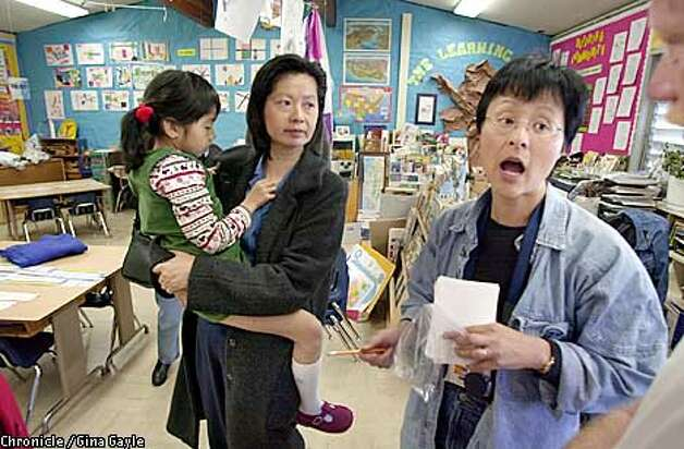 Andi Wong,(r) parent coordinator of the parent run art program at Rofftop Elementary school talks about an issue up for discussion at the PTA meeting that night. Andi and Melody Lem, holding daughter Kelsey, and other parents had just finished helping children's frst grade class with their production of The Three Billy Goats Gruff. Photo by Gina Gayle/The SF Chronicle. Photo: GINA GAYLE