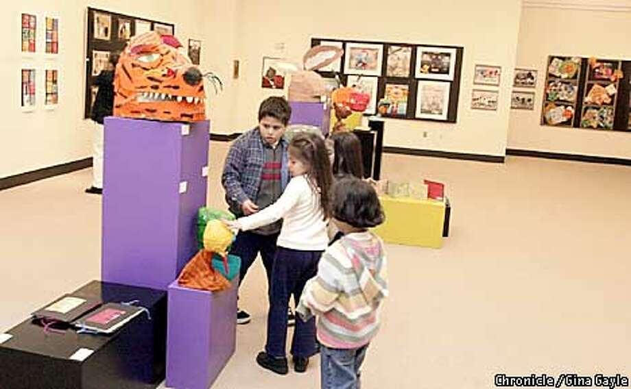 OUTREACHXXc-C-21MAR02-DD-GG-Some young people from the community admire the artwork during Art is Education Community Reception at the State of California Office Building. Noelle is a student at Ascend school. Photo by Gina Gayle/The SF Chronicle.