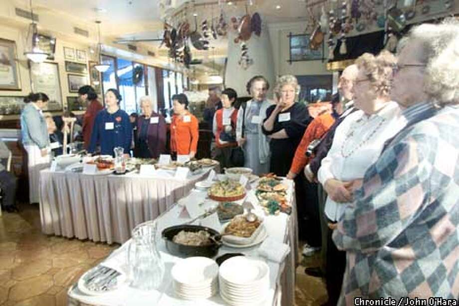 Contestants hold their dishes and await the judges' decisions in the senior cook-off at Cafe Pescatore. Chronicle photo by John O'Hara