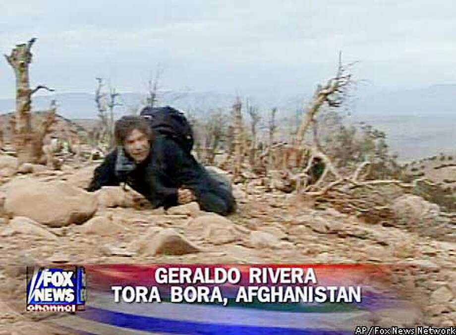 This image taken from television and released in New York shows Fox News Channel correspondent Geraldo Rivera in Afghanistan on Thursday, Dec. 6, 2001. Rivera was taping a report on a ridge near Jalalabad when he was fired upon by a sniper. A Fox spokesperson said that the sound of bullets was picked up by his crew's microphone. (AP Photos/Fox News Network)