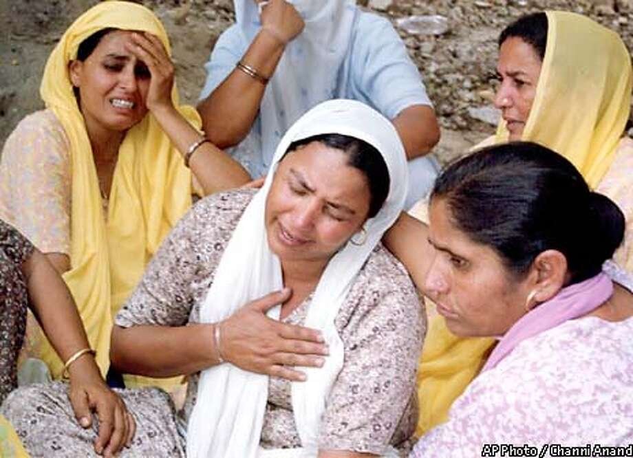 Family members weep for their relatives who were killed in Jammu, India, Tuesday May 14, 2002. Susupected Islamic Militants shot and killed at least 30 civilians and soldiers in an exchange of gunfire that took place at an Indian army base in Kashmir. (AP Photo/Channi Anand) Photo: CHANNI ANAND