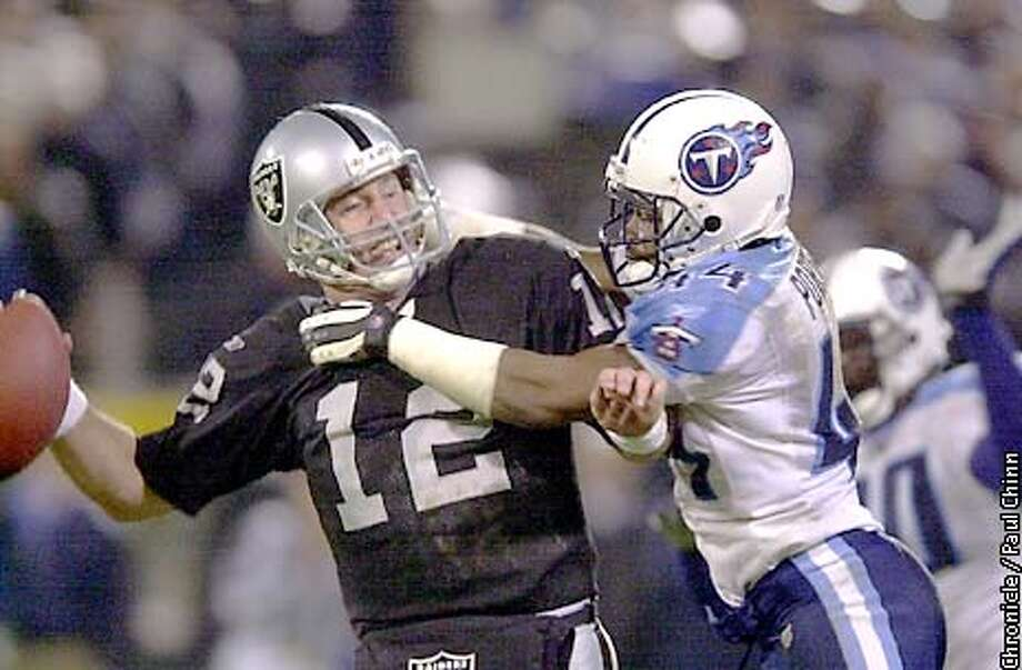 Raiders' quarterback, Rich Gannon, comes under pressure by Daryl Porter in the fourth quarter.  The Oakland Raiders played the Tessessee Titans at Network Associates Coliseum in Oakland, Ca., on Saturday night, December 22, 2001. (PAUL CHINN/SAN FRANCISCO CHRONICLE) Photo: PAUL CHINN