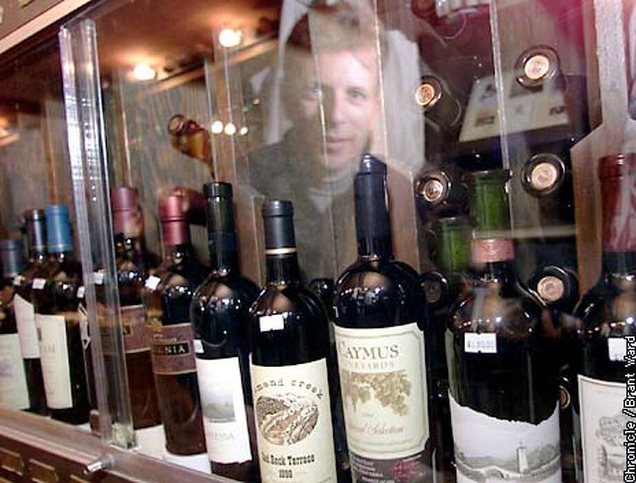 Frank Melis, the wine director of the Cannery Wine Cellar, is reflected in a glass case of expensive wines he sells in San Francisco. These are some of the labels that have gone up in price tremendously since they first hit the shelves, now finding a place in a locked glass cabinet. By Brant Ward/Chronicle Photo: BRANT WARD