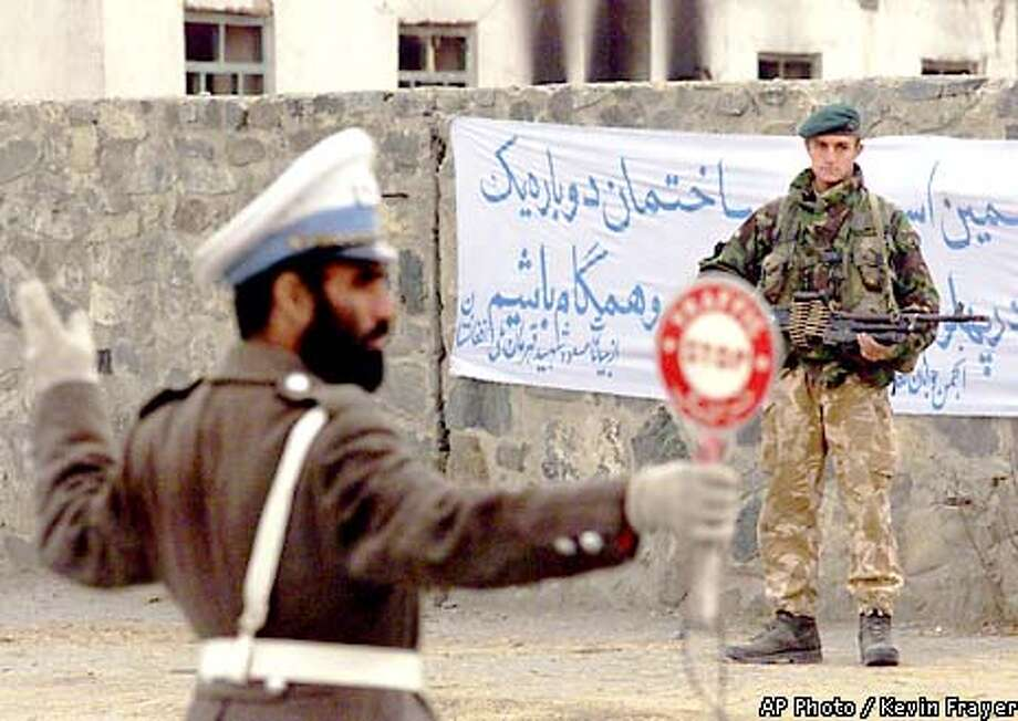 A British Royal Marine peacekeeper, right, stands guard as a police officer directs traffic in the Afghan capital of Kabul Saturday Dec. 22, 2001. The British troops took to the streets as Afghanistan's new government was sworn in. (AP Photo/CP, Kevin Frayer) Photo: KEVIN FRAYER