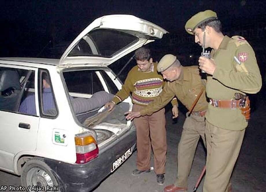 Police officers search the trunk of a private car during a surprise check by Indian security agencies in Jammu, India, Friday, Dec. 21, 2001. India said Friday it would recall its ambassador from Pakistan and terminate rail and bus links between the two nations, after a suicide attack that New Delhi blames on Islamabad. The actions will take effect on Jan. 1, 2002. (AP Photo/Aijaz Rahi) Photo: AIJAZ RAHI
