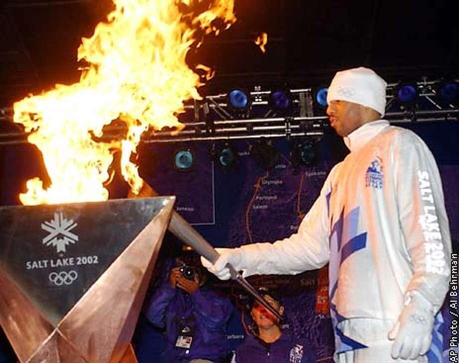 New Jersey Nets forward Kenyon Martin lights the Olympic flame after running the last leg of the , Monday, Dec. 17, 2001, in Cincinnati. (AP Photo/Al Behrman) Photo: AL BEHRMAN