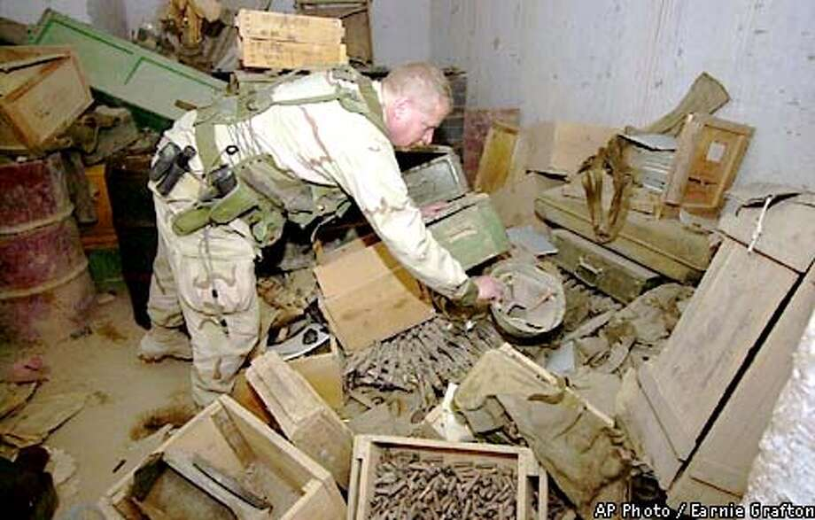 Navy Chief Petty Officer Jon Scott, of Virginia Beach, Va., picks a helmet out of a pile of munitions found in a building at Kandahar Airport in Afghanistan, Friday, Dec. 21, 2001. Tons of munitions are being located by explosive ordnance teams and destroyed. (AP Photo/Earnie Grafton, Pool) Photo: EARNIE GRAFTON