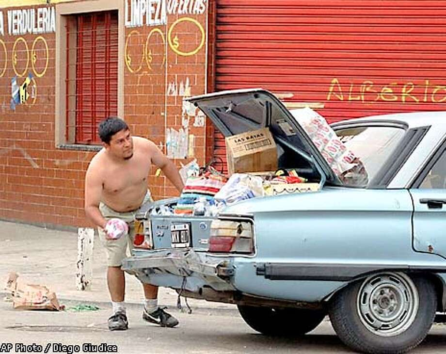 A man loads the truck of his car with looted merchandise from a food market on the outskirts of Buenos Aires, Wednesday, Dec. 19, 2001. Jobless Argentines stormed supermarkets, shops and kiosks on Wednesday as Argentina's long-festering economic crisis boiled over on the poor fringes of Buenos Aires.(AP Photo/Diego Giudice) Photo: DIEGO GIUDICE