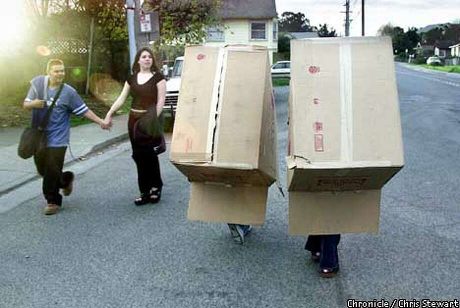 """Two Petaluma teenagers carried home a couple of appliance cartons from a store in Petaluma last week, much to the amusement of two young passersby. Mallory O'Hara (left box) and Amanda Lorenzen (right, trust us) said that after using the giant cartons for gift packaging, the two 16-year-olds friends would """"use them to slide down a hill."""" Chronicle photo by Chris Stewart"""