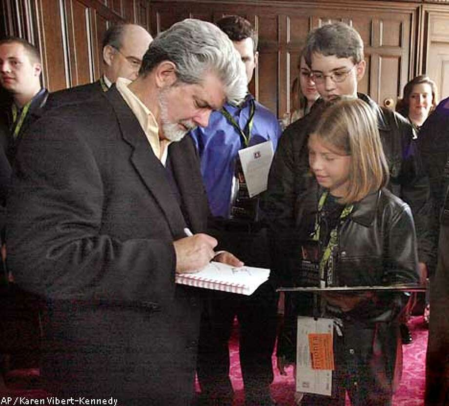 """Director George Lucas, left, signs autographs for families of the California Mentor Program and the Make-A-Wish Foundation before the charity premiere of """"Star Wars: Episode II Attack of the Clones"""" in San Francisco, Sunday, May 12, 2002. (AP Photo/Karen Vibert-Kennedy, Pool) Photo: KAREN VIBERT-KENNEDY"""