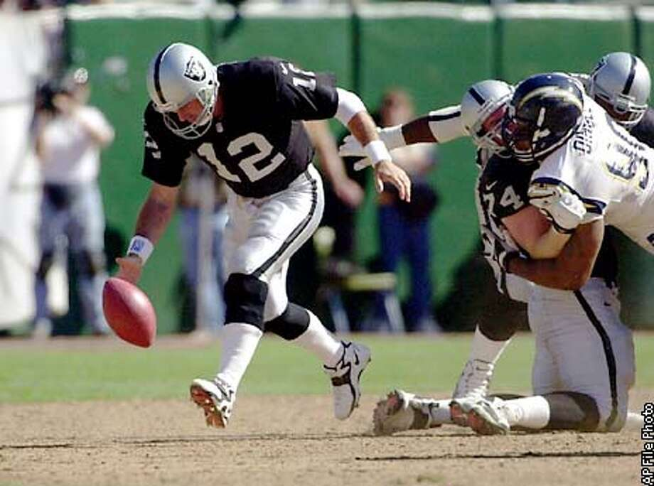 After being stripped of the ball, Oakland Raiders quarterback Rich Gannon (12) picks it up and runs 15 yards to set up his game-winning touchdown pass late in the fourth quarter against the San Diego Chargers on Sunday, Sept. 3, 2000, in Oakland, Calif. At right are Raiders' Matt Stinchcomb (74) and Chargers' Adrian Dingle. The Raiders win 9-6. (AP Photo/Bob Galbraith) Photo: BOB GALBRAITH