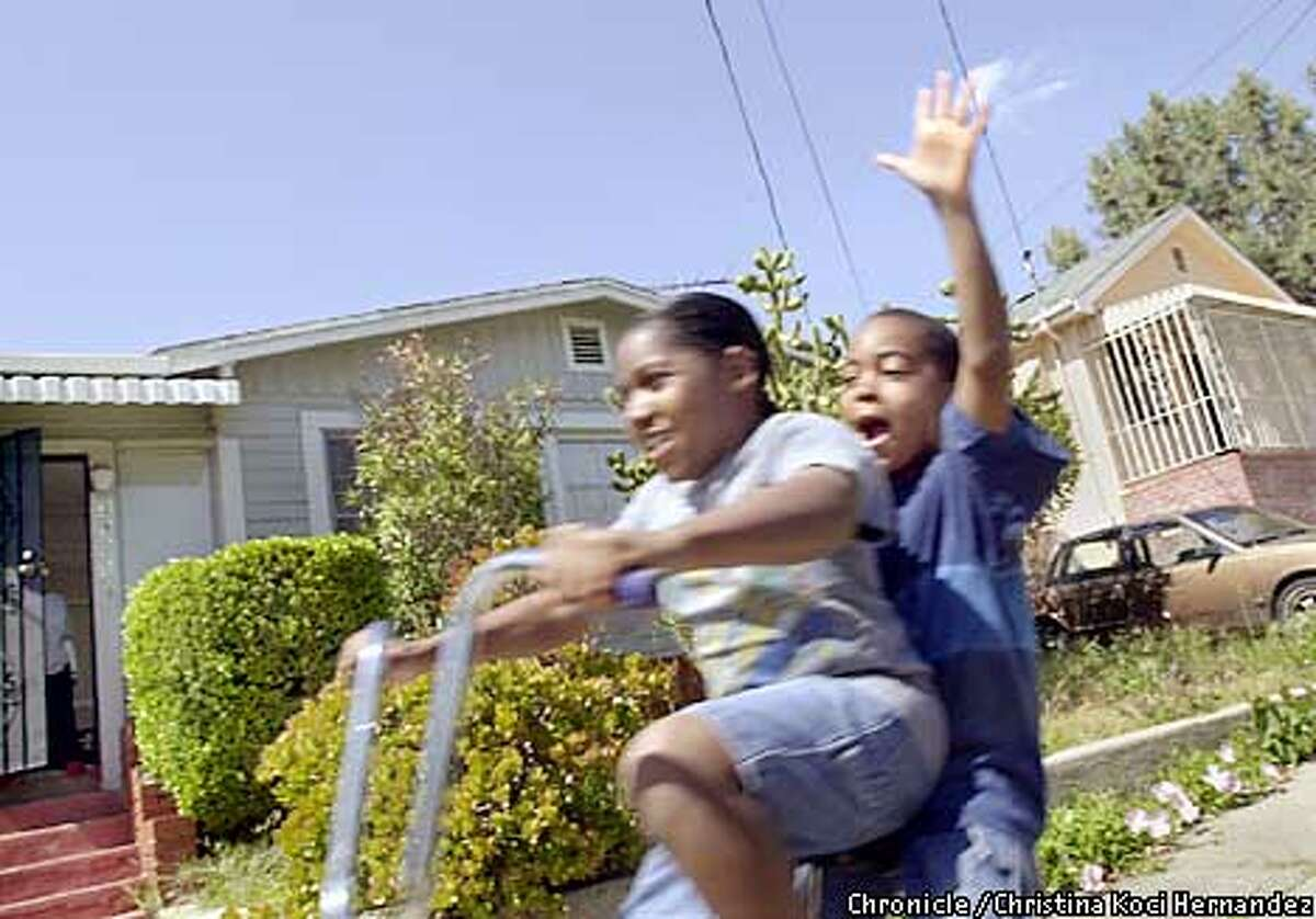 CHRISTINA KOCI HERNANDEZ/CHRONICLE In front of her Laurel District home, in Oakland, (driving bike) Britni Black, age 11, and cousin, Joedy Sadler,( of Oakland but doesn't live in the Laurel), age 9, enjoy a ride down the hills of the neighborhood. Looking at Oakland's Laurel district in regards to race and ethnicity.