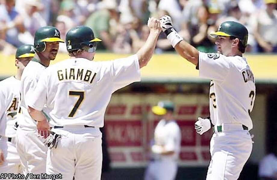 Oakland Athletics' Eric Chavez, right, is congratulated at home plate by teammates Jeremy Giambi (7) and Terrence Long after hitting a grand slam off of Toronto Blue Jays pitcher Justin Miller in the second inning Saturday, May 11, 2002, in Oakland, Calif. (AP Photo/Ben Margot) Photo: BEN MARGOT
