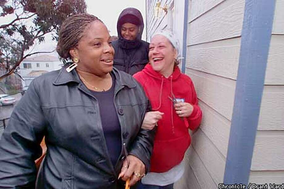 Turning the corner on new lives, Donna Doyle, left, and Michele Williams prepare to enter their new homes built by Habitat for Humanity. Although they can't move in just yet, the two are looking forward to moving their families into the new homes in the Bayview District before Christmas. By Brant Ward/Chronicle Photo: BRANT WARD