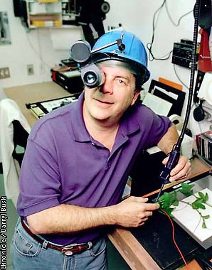 """Robert Buelteman wears a night vision scope in his darkroom where he works on his """"art pieces"""" using plant subjects, in his Montara studio. Chronicle Photo by Darryl Bush Photo: Darryl Bush"""