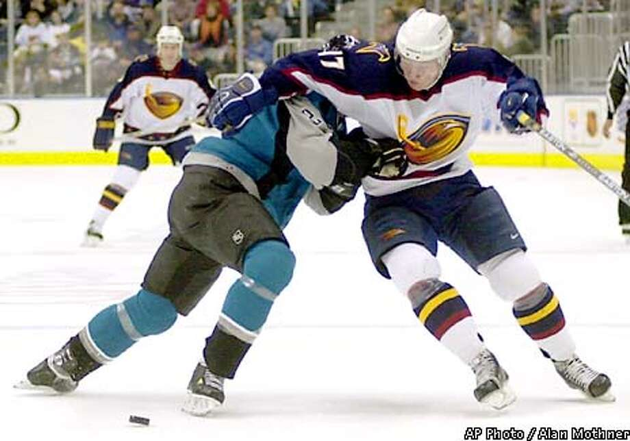 Atlanta Thrashers left wing Ilya Kovalchuk, right, of Russia, pushes his way past San Jose Sharks defenseman Mike Rathje during the first period in Atlanta, Wednesday, Dec. 19, 2001. (AP Photo/Alan Mothner) Photo: ALAN MOTHNER