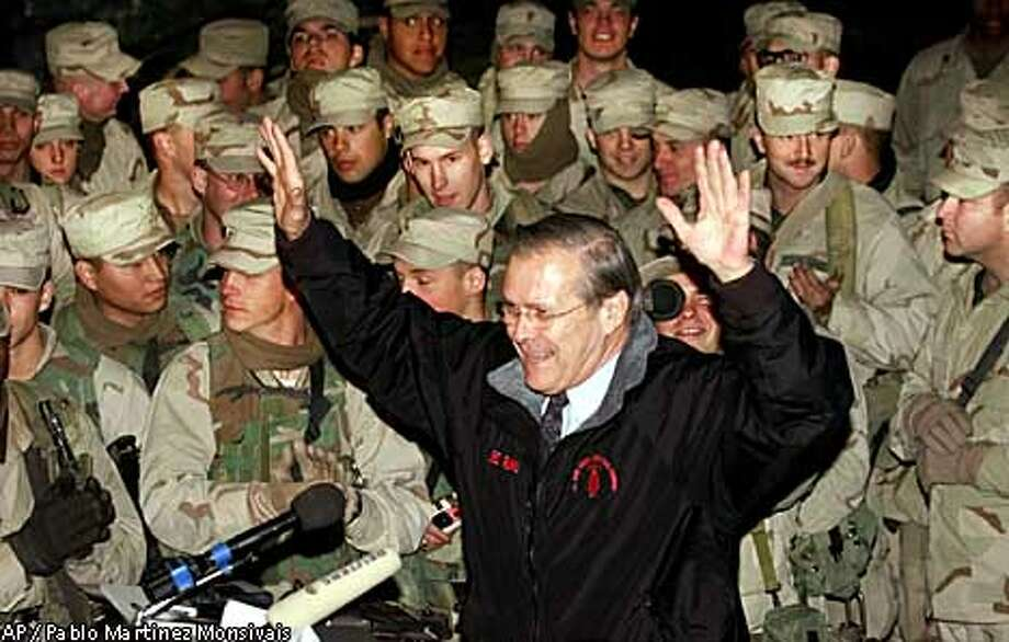 U.S. Secretary of Defense Donald Rumsfeld threw up his arms as he ended a meeting with U.S. troops at Bagram air base in Afghanistan. Associated Press photo by Pablo Martinez Monsivais
