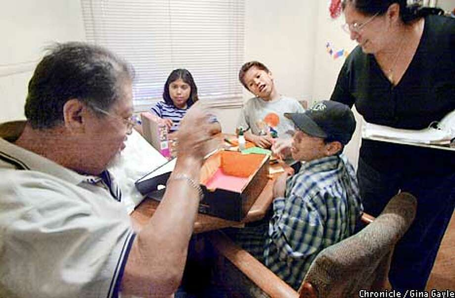 Joe and Josephine Basulto help their three grandchildren with homework at their Pittsburg home. From front Marco Diaz,12, Vincent Alvarez,7, and Nicole Diaz,10. Photo by Gina Gayle/The SF Chronicle. Photo: GINA GAYLE