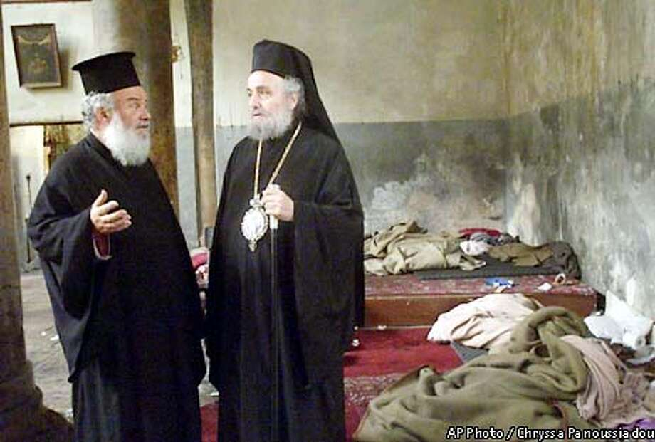 Greek Orthodox Patriarch Irineos I, right, talks with an unidentified priest as they inpect the damage to the Church of the Nativity in the West Bank town of Bethlehem, Friday, May 10, 2002. The 39-day standoff at the Church of the Nativity ended Friday with 13 militant Palestinians leaving the church and being flown to exile. Twenty-six others were transferred to Gaza. (AP Photo/POOL, Chryssa Panoussiadou) Photo: CHRYSSA PANOUSSIADOU