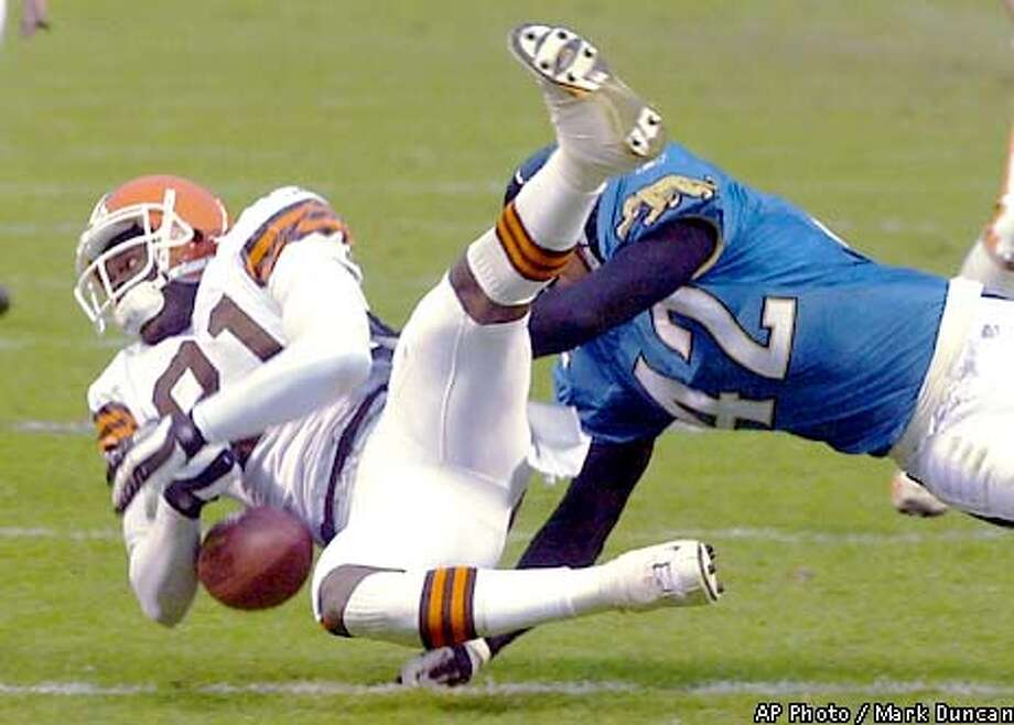 Cleveland Browns receiver Quincy Morgan (81) bobbles the football as he is hit by Jacksonville Jaguars defender James Boyd late in the fourth quarter Sunday, Dec. 16, 2001, in Cleveland. Originally ruled a catch for a first down, the play was later overturned on replay to give the ball to Jacksonville on downs with 48 seconds left. The game was then halted when fans began to throw debris on the field. (AP Photo/Mark Duncan) Photo: MARK DUNCAN