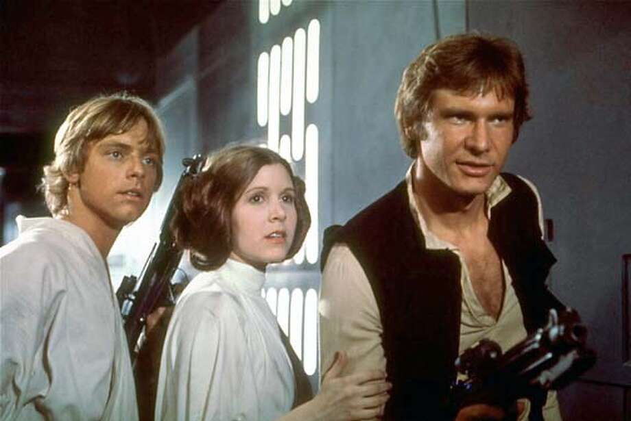 "Mark Hamill as Luke Skywalker, Carrie Fisher as Princess Leia and Harrison Ford as Han Solo in 1977's ""Star Wars."""