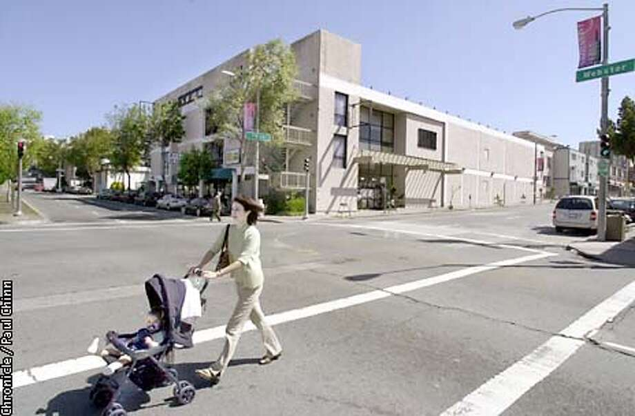 A woman pushed a stroller across Webster street across from the Japantown Bowl (background). Developers are planning residential units on the top floors and retail space on the ground floor of the old bowling alley site at Post and Webster Sts.  PAUL CHINN/S.F. CHRONICLE Photo: PAUL CHINN