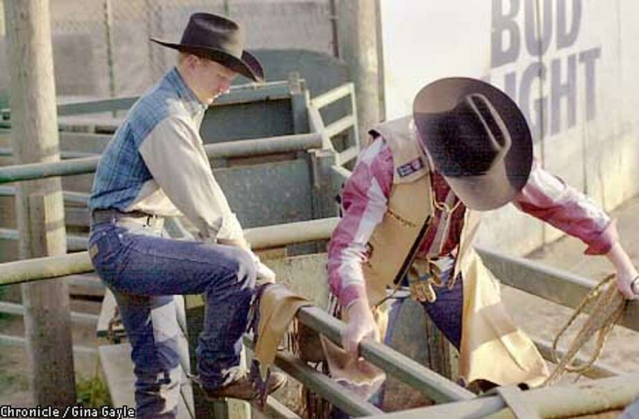 Brad Gentrup helps his friend Austin Schwartz get situated in the chute before a practice bull riding session at a ranch in Morgan hill where the two men along with their other friend Kevin Willis pratice. The three friends usually practice and travel together to the rodeos. Photo by Gina Gayle/The SF Chronicle. Photo: GINA GAYLE