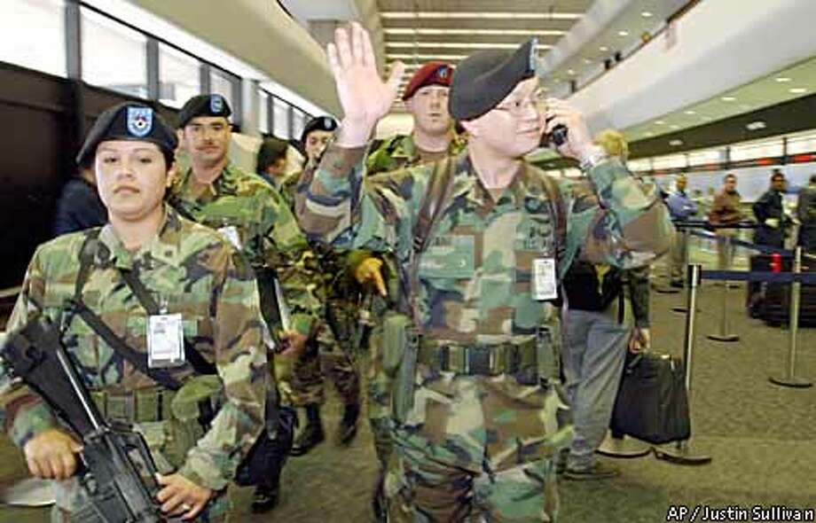 National Guardsman Sgt. Jared Yang, right, waves to cheering airline workers as Guard members leave SFO on their last day of duty Friday. Associated Press photo by Justin Sullivan